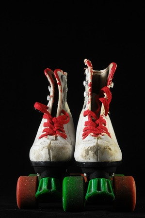 Used Vintage Consumed Roller Skate on a Black Background photo