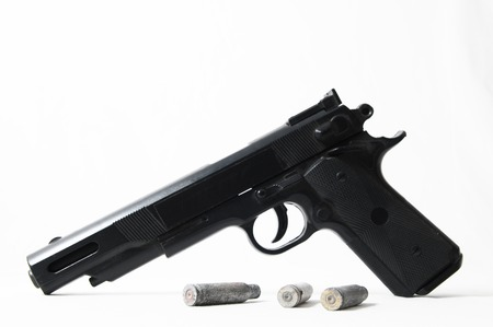 Pistol Gun and Bullets on a White Background photo