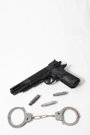 Pistol Gun and Handcuffs on a White Background photo