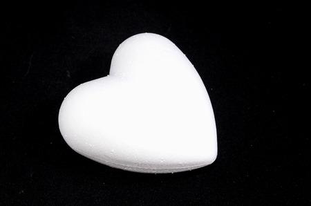 cupido: White Polystyrene Heart on a Black Background