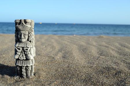 Ancient Maya Statue on the Sand Beach near Ocean photo