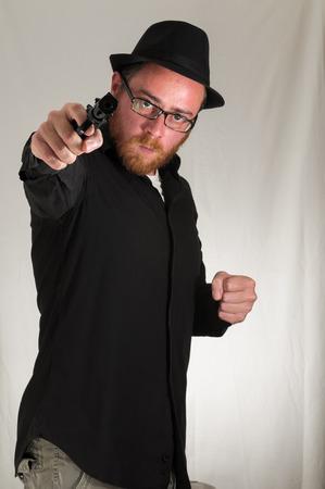 Black Dressed Young Man Holding a Pistol Gun photo