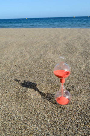 One Hourglass on the Sand Beach Near the Ocean Time Concept Stock Photo