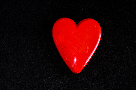 Red Heart Made of Stone on Black Background photo