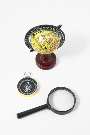 Vintage Tools Globe Compass and Loupe on a White Background