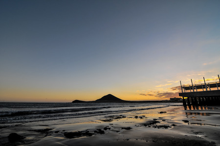 Sunset on the Atlantic Ocean with a Mountain in Background El Medano Tenerife Canary Islands Spain photo