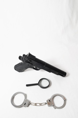 Gun and Handcuffs on a White Background photo