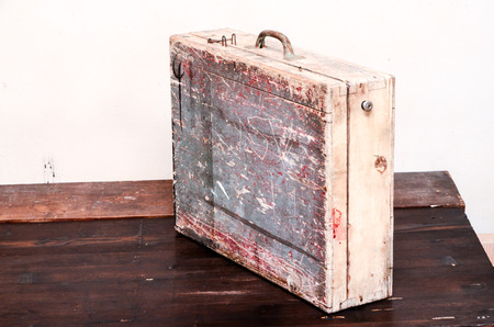 Vintage Wood Colored Brown Suitcase on Wooden Table photo