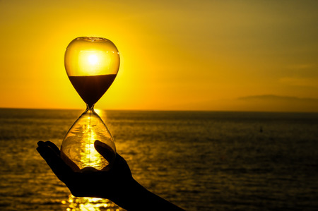 Time Concept Hourglass and Sun Setting on the Atlantic Ocean