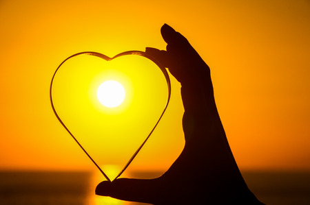 Love Concept Heart and Sun Setting on the Atlantic Ocean Stock Photo