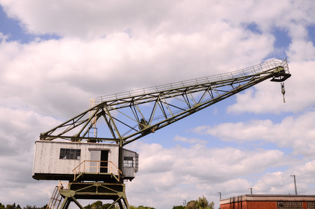 Old Vintage Wooden Port Crane on a Cloudy Blue Sky photo