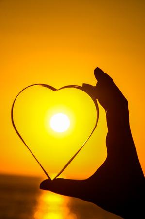 Love Concept Heart and Sun Setting on the Atlantic Ocean photo