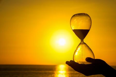 時間概念の砂時計と大西洋に沈む夕日