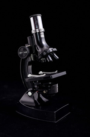 Old Vintage Microscope Isolated Over Black Background photo
