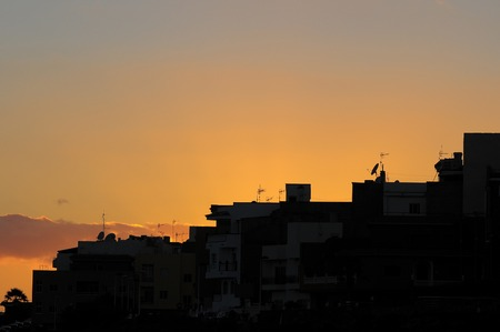 Silhouettes of Houses at Sunset over a Sea Village photo