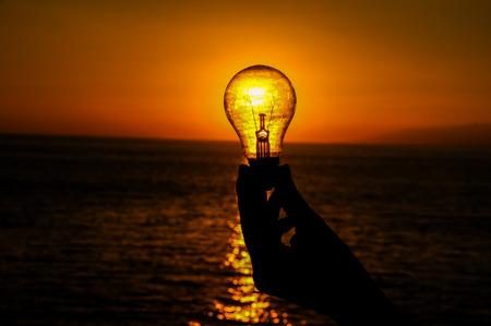Energy Concept Light Bulb and Sun Setting on the Atlantic Ocean Stock Photo
