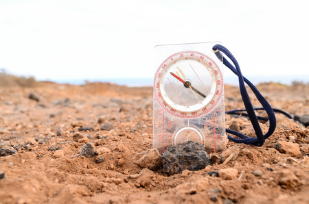 Orientation Concept Metal Compass on a Rock in the Desert photo