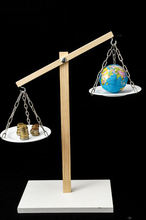 Globe Planet Earth and Money on a Two Pan Balance photo