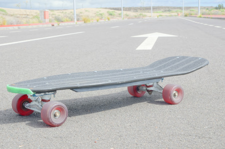 longboard: Vintage Style Longboard Black Skateboard on an Empty Asphalt Desert Road