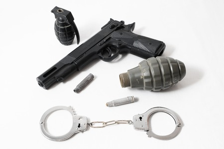 Grenade Bullets Gun and Handcuffs on a White Background photo