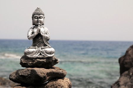 One Ancient Gray Buddha Statue Near The Ocean photo