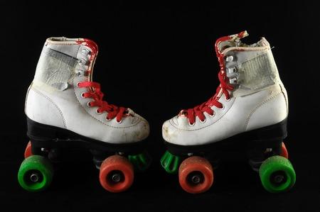 Used Vintage Consumed Roller Skate on a Black Background photo