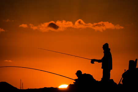 Fisherman Fishing Rod Silhouette at Orange Sunset photo