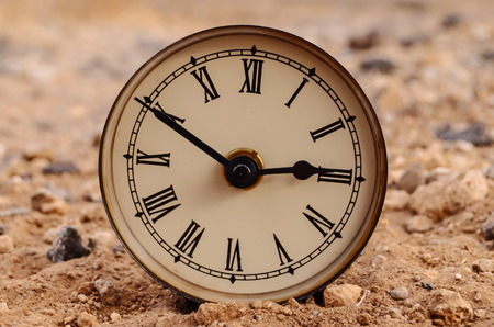 Classic Analog Clock In The Sand On The Rock Desert photo
