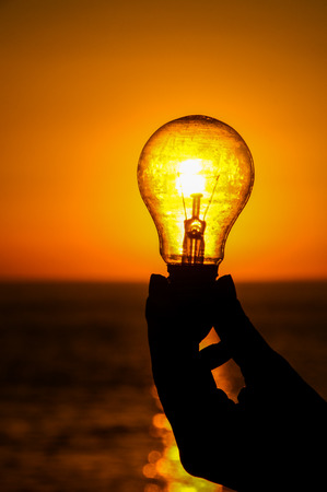 Energy Concept Light Bulb and Sun Setting on the Atlantic Ocean Imagens
