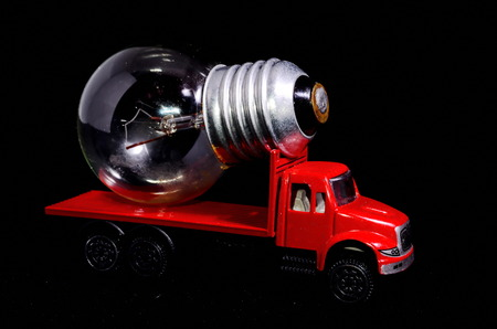 electric bulb: Electric Power Concept Red Truck and Light Bulb on a Black Background Stock Photo