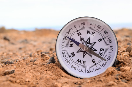 Orientation Concept Metal Compass on a Rock in the Desert Stock Photo