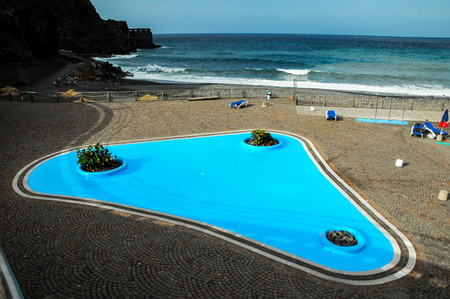 vallehermoso: Blue Swimming Pool near the Atlantic Ocean Stock Photo