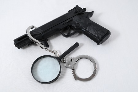 criminality: Criminality Concept Gun and Handcuffs on a White Background