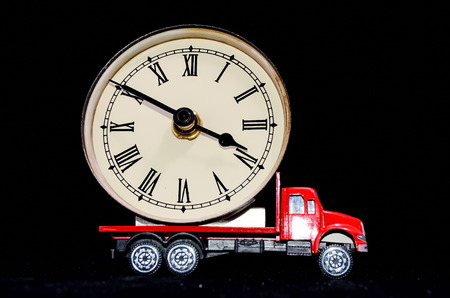 Time Transportation Concept Clock Watch on a Red Toy Truck over Black Background photo