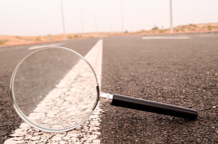 Travel Concept Magnify Glass Loupe on the Asphlat Road photo