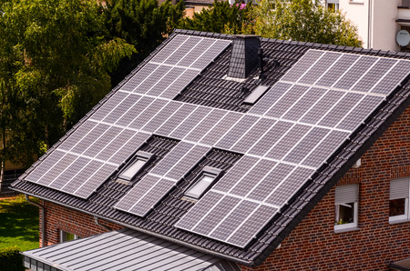 Green Renewable Energy with Photovoltaic Panels on the Roof. Stock Photo