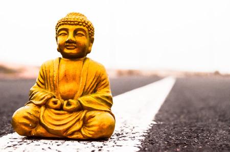 Ancient Buddha Statue on the Asphalt Road