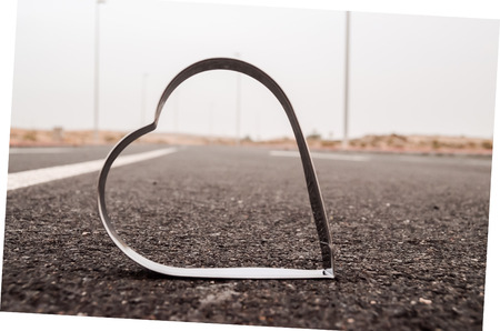 highway love: Heart Symbol on the Grainy Asphalt Texture. Love for Travel Concept