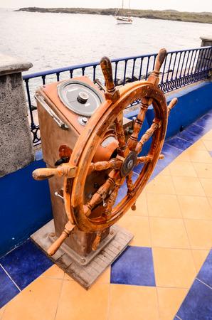 Old Vintage Wooden Helm Wheel near Blue Ovcean photo