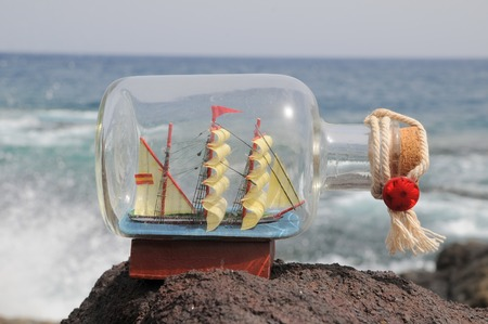 Zeilschip in de fles in de buurt van de oceaan Stockfoto