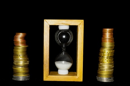 buisness: Buisness Time Concept Hourglass and Money on a Black Background
