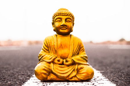 Ancient Buddha Statue on the Asphalt Road photo
