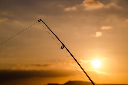 Fisherman Fishing Rod Silhouette at Orange Sunset photo