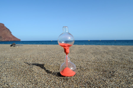 timelapse: One Hourglass on the Sand Beach Near the Ocean Time Concept Stock Photo