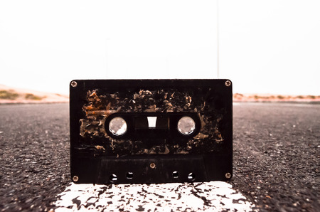 cassette tape: Ancient Retro Musicassette on the Asphalt Road
