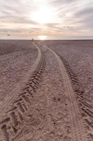 Wheel Tracks in the Sand of a Sandy Beach Desert photo