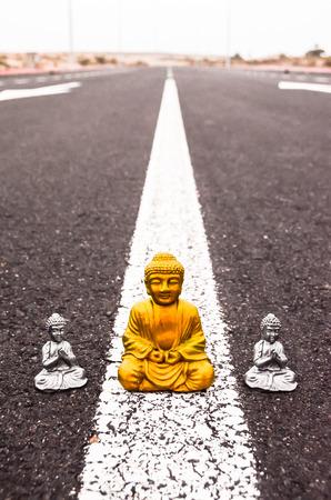 buddha statue: Ancient Buddha Statue on the Asphalt Road