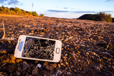 White Smartphone with Broken Display in the Desert photo