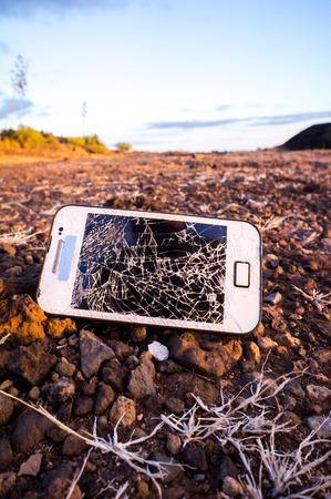 White Smartphone with Broken Display in the Desert