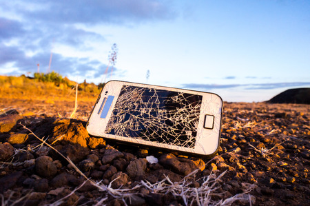White Smartphone with Broken Display in the Desert